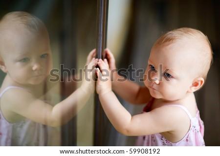 Outdoor casual portrait of adorable baby girl standing by glassed door - stock photo