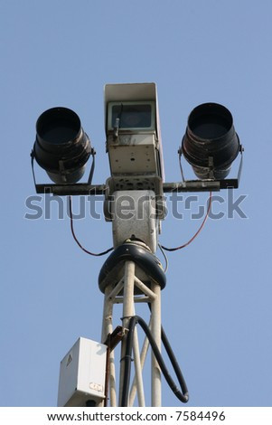 Outdoor CCTV camera with infrared lights with a clear blue sky background