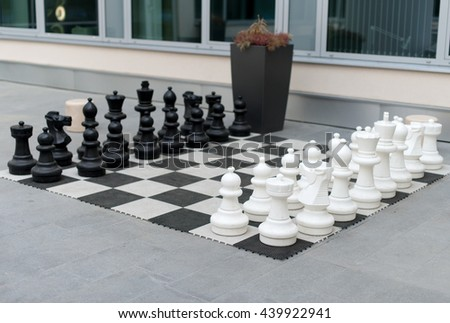 Outdoor chess board with big plastic figures. - stock photo
