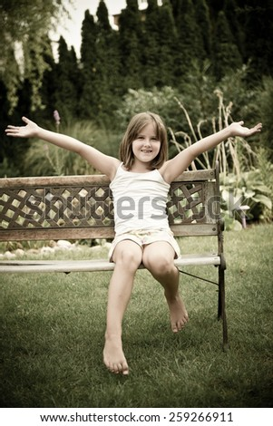 Outdoor child portrait - happy smiling girl sitting on bench, legs and hands stretched - stock photo