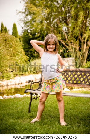 Outdoor child portrait - little girl sitting on bench outdoor in backyard - stock photo