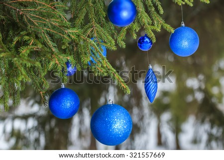 Outdoor Christmas turquoise sparkle bauble ornaments are hanging on snowy spruce twig - stock photo