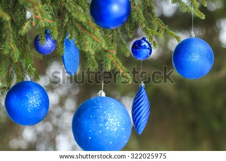 Outdoor Christmas ultramarine tinsel baubles are hanging on snowy spruce twig - stock photo