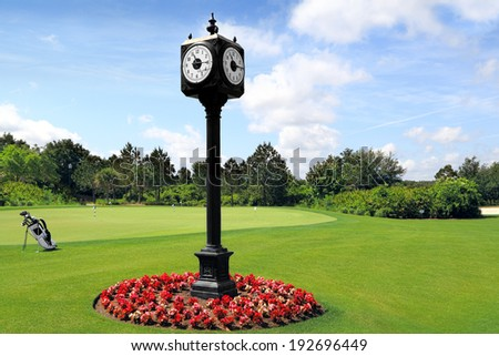Outdoor Clock Post on golf course with green spring valley on the background - stock photo