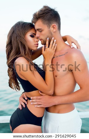 Outdoor close up fashion portrait of pretty sexy couple in love  hugs on  amazing tropical  beach, wearing stylish swimwear.