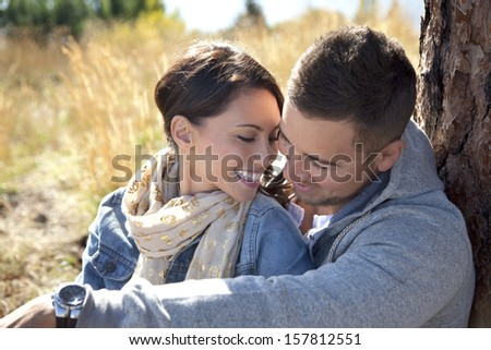 Outdoor close-up photo of young couple seated in grassy field. - stock photo