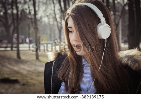 Outdoor close up portrait of a pretty teenage girl with headphones. Toned effect - stock photo