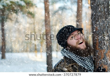 Outdoor Close up portrait of cheerful handsome bearded man enjoying the snowfall in winter forest - stock photo