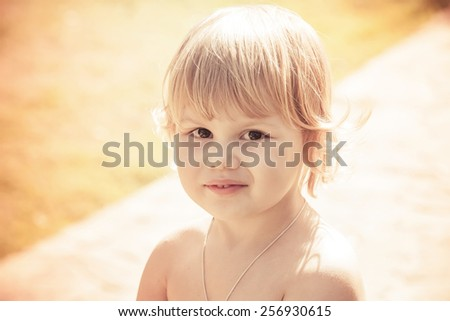 Outdoor close-up portrait of cute smiling Caucasian blond baby girl. Vintage toned photo with instagram orange toning filter effect - stock photo