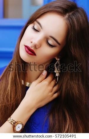 Ngoài trời đóng lên bức chân dung của cô gái trẻ xinh đẹp.  Mẫu nhắm mắt lại.  trang điểm xinh đẹp, mái tóc dài, phong cách cổ tay đồng hồ, phụ kiện.  Nữ vẻ đẹp, khái niệm thời trang.  ánh sáng ngày, nền màu xanh