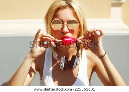 Outdoor closeup colorful portrait of young pretty blonde woman eating ice cream with headphones listening to the music in summer  - stock photo