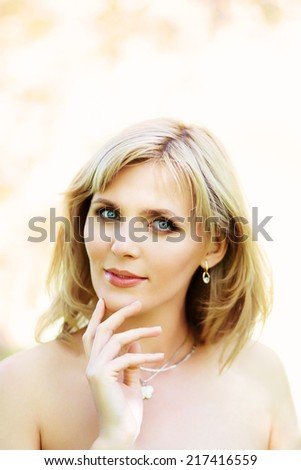 outdoor closeup portrait of a beautiful blonde middle aged woman - stock photo