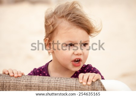 Outdoor closeup portrait of cute blond baby girl with wind in her hair - stock photo
