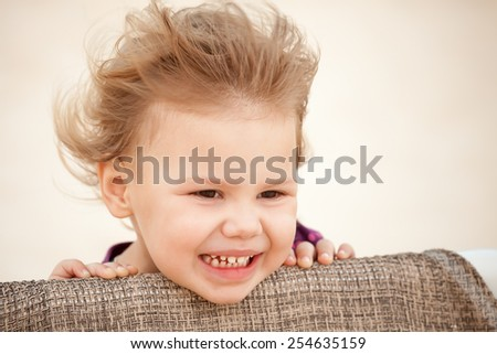 Outdoor closeup portrait of cute Caucasian blond baby girl with wind in her hair - stock photo