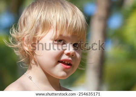 Outdoor closeup portrait of cute smiling Caucasian blond baby girl - stock photo