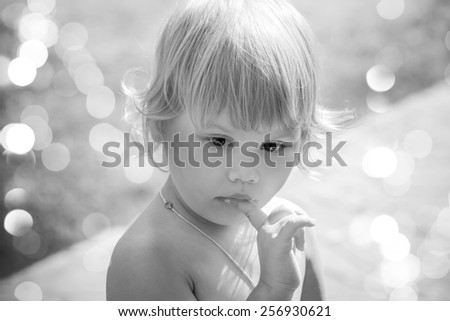 Outdoor closeup portrait of cute thinking Caucasian blond baby girl. Vintage toned photo with instagram retro toning filter effect - stock photo