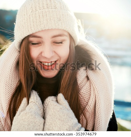Outdoor closeup portrait of pretty young sensual smiling woman with closed eyes posing on snow in winter