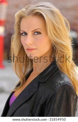 Outdoor closeup portrait of serious woman - stock photo