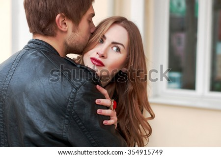 Outdoor closeup portrait of young sensual couple in love posing on the street in spring boyfriend kissing her girlfriend