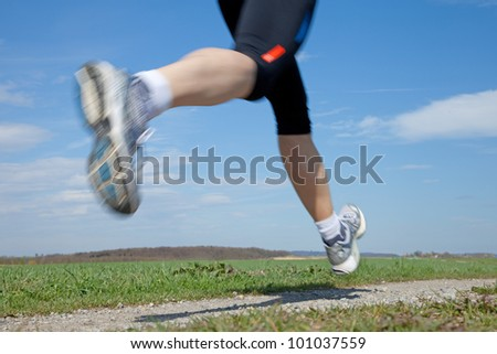Outdoor closeup shot of a male runner running at a fast pace - stock photo
