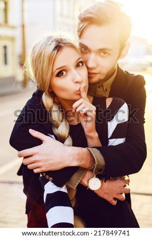 Outdoor closeup summer portrait of pretty fashion hipster couple in love posing on the street girl shows with finger to make silence  - stock photo