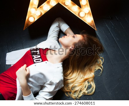 Outdoor colorful portrait of pretty smiling happy sensual hipster style woman going crazy and lying on the floor near star.Fashion portrait of young singer lying on floor with long curly blonde hair.