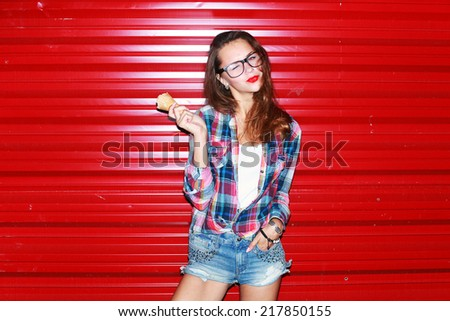 Outdoor colorful portrait of pretty young sexy woman posing and having fun in the night eating ice-cream with her nice red lips on urban style background  - stock photo
