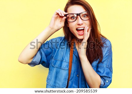 Outdoor colorful summer portrait of pretty smiling happy sensual hipster style woman going crazy and shocked and saying hello on yellow background  - stock photo