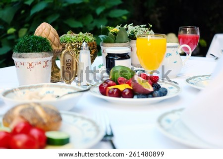 Outdoor continental breakfast at hotel. Shallow depth of field. No brandnames or copyright objects.  - stock photo