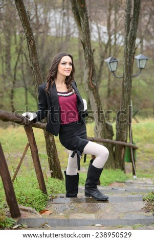 Outdoor country style fashion portrait of a beautiful long-haired blond young woman posing on a wooden bridge