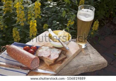 outdoor dining :  ( picnic ) with salami, bread,butter,tomatoes and a wheat beer. - stock photo