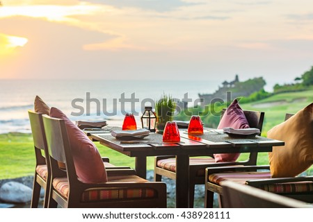 Outdoor dinner setting at sunset overlooking the coastline of a beautiful tropical Island. - stock photo