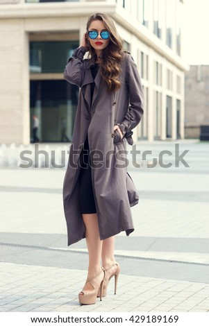 Outdoor dynamic fashion portrait of young beautiful stylish woman in black dress, grey coat and sunglasses walking on a windy day against city background - stock photo