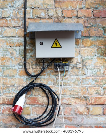 Outdoor Electric control cabinet for electrical equipment on brick wall with wires and plug jack. Knife switch on old dirty wall/Grey electrical box on wall background  - stock photo