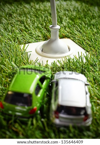 Outdoor electrical power socket in green grass with a plug and cable inserted and two toy model cars in the foreground