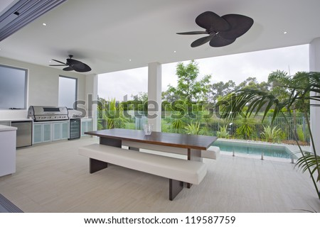 Outdoor entertaining area with swimming pool - stock photo