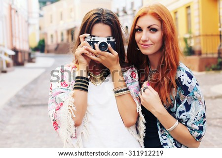 Outdoor fall smiling lifestyle portrait of pretty young girls having fun in the city in Europe. Making pictures in hipster style, taking pictures on retro camera, wearing stylish vintage boho outfits. - stock photo