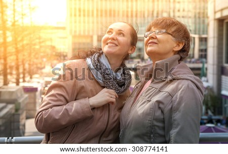Outdoor family portrait of pension age Mother and her daughter in the city, smiling and looking around. Two generation, happiness and care  concept - stock photo