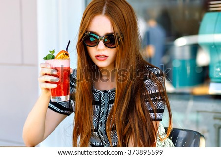 Outdoor fashion beauty portrait of glamour elegant lady, amazing long hairs, luxury vintage dress and cat eye sunglasses, drinking tasty cold cocktails, city cafe terrace, travel, joy, relax. - stock photo
