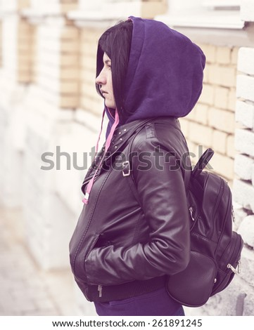 Outdoor fashion brunette stands in the hood black leather jacket and a backpack - stock photo