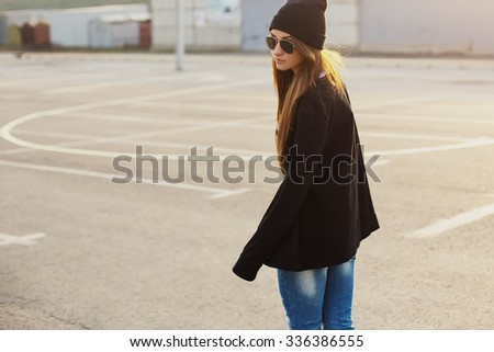 Outdoor fashion closeup portrait of nice pretty young hipster woman walks along at the streets of the city at sunset . - stock photo