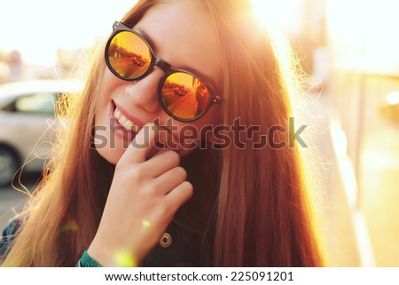 Outdoor fashion closeup portrait of pretty young woman in the city in evening in hipster style glasses. Photo toned style Instagram filters. - stock photo