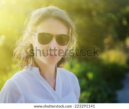 Outdoor fashion closeup portrait of young pretty woman in sunglasses - stock photo