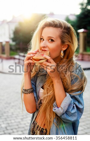 Outdoor fashion hipster style portrait of beautiful blonde woman eating tasty hamburger on the street smiling having fun  - stock photo
