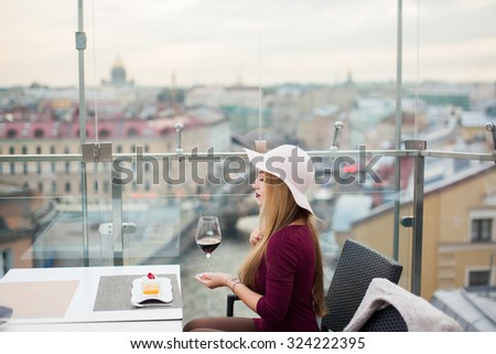 Outdoor fashion image of sensual young woman drinking red wine at lounge bar cafe with amazing view of the city,fashionable stylish glamour model girl,fancy girl,accessory store,jewelry golden   - stock photo