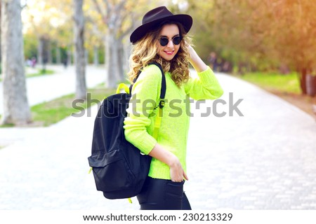 Outdoor fashion image of stylish hipster girl wearing neon sweater sunglasses and vintage hat, walking with back pack on the street in nice sunny fall autumn day. - stock photo