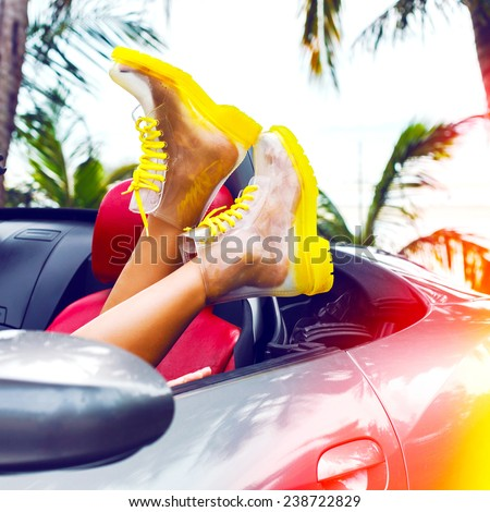 Outdoor fashion image of woman legs in creative clear boots, laying at luxury car, wis on palms, hot tropical country. Bright instagram colors. - stock photo