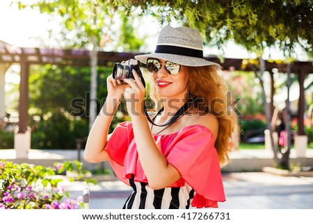 Outdoor fashion image of Young woman traveler with vintage camera,summer dress,ready of her holidays,girl photographer holding camera,make pictures of her trip,pink style clothes,vacation - stock photo
