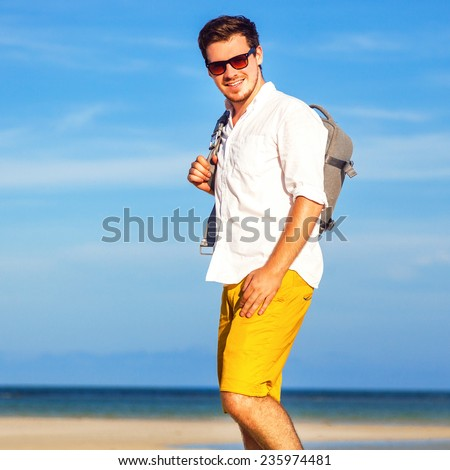 Outdoor fashion lifestyle image of young traveler handsome hipster man, wearing bright yellow shorts sunglasses, and holding his backpack, ready for adventures. Amazing view on beach and blue sky. - stock photo