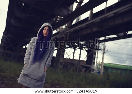 Outdoor fashion lifestyle portrait of pretty young girl, wearing in hipster swag grunge style with violet hair urban background
